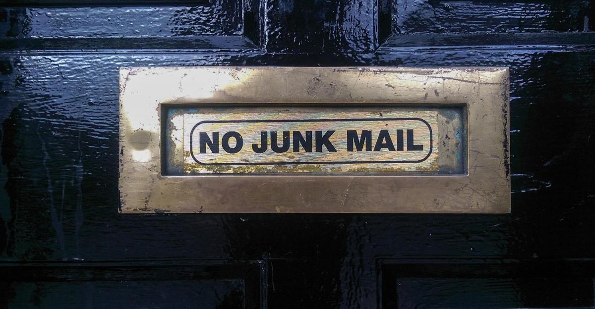 No Junk Mail written on the mailbox window of this door.